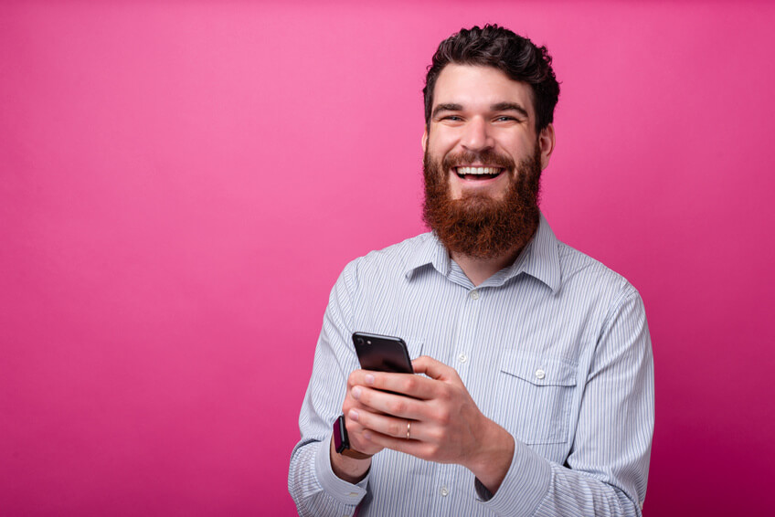 Smiling man with msartphone on his hand looking at the camera app